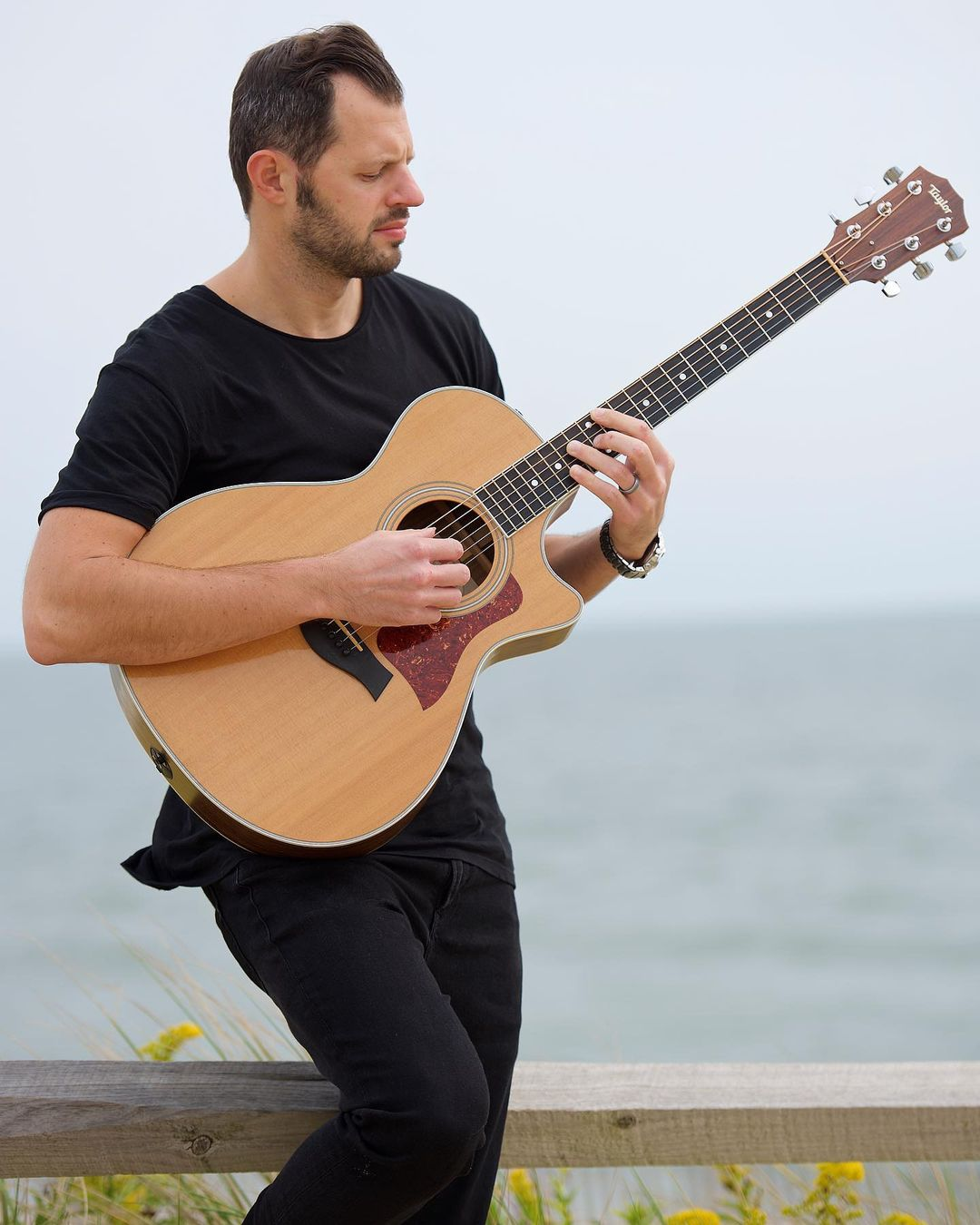 LBI Anthony Michael strumming his six-string on beach.      …